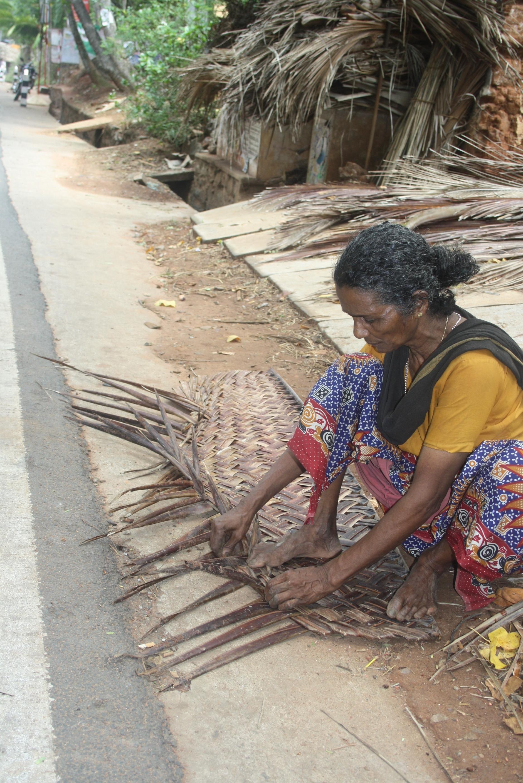 Eine Frau flechtet Palmenwedel zu Körben zusammen